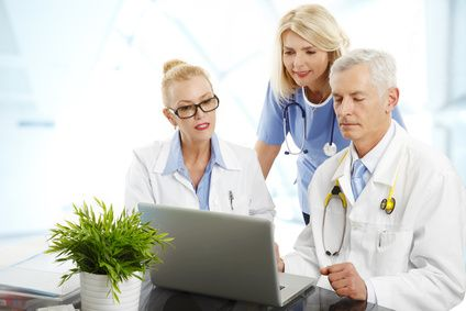 Portrait of medical staff sitting at hospital. Doctors and nurse sitting in front of computer and consulting.