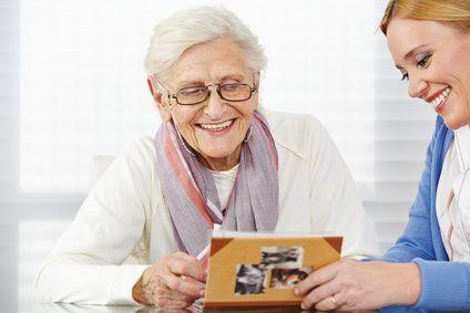 Lächelnde Seniorin schaut Fotos im Fotoalbum an mit ihrer Tochter